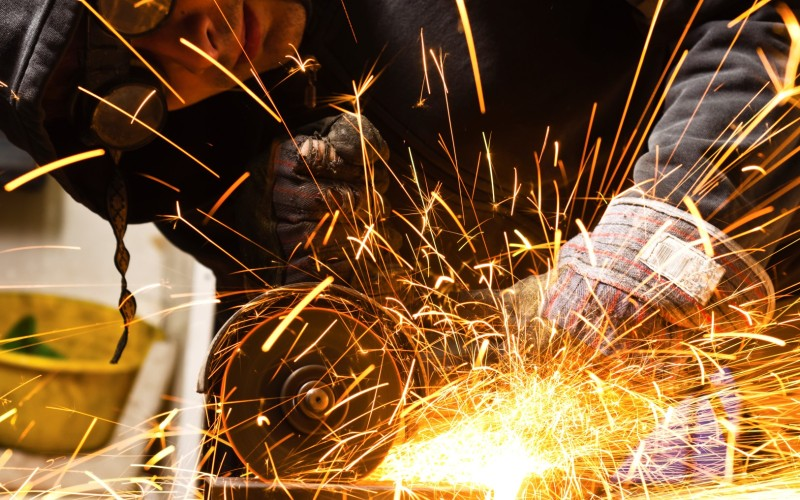 Welder cutting iron with sparks
